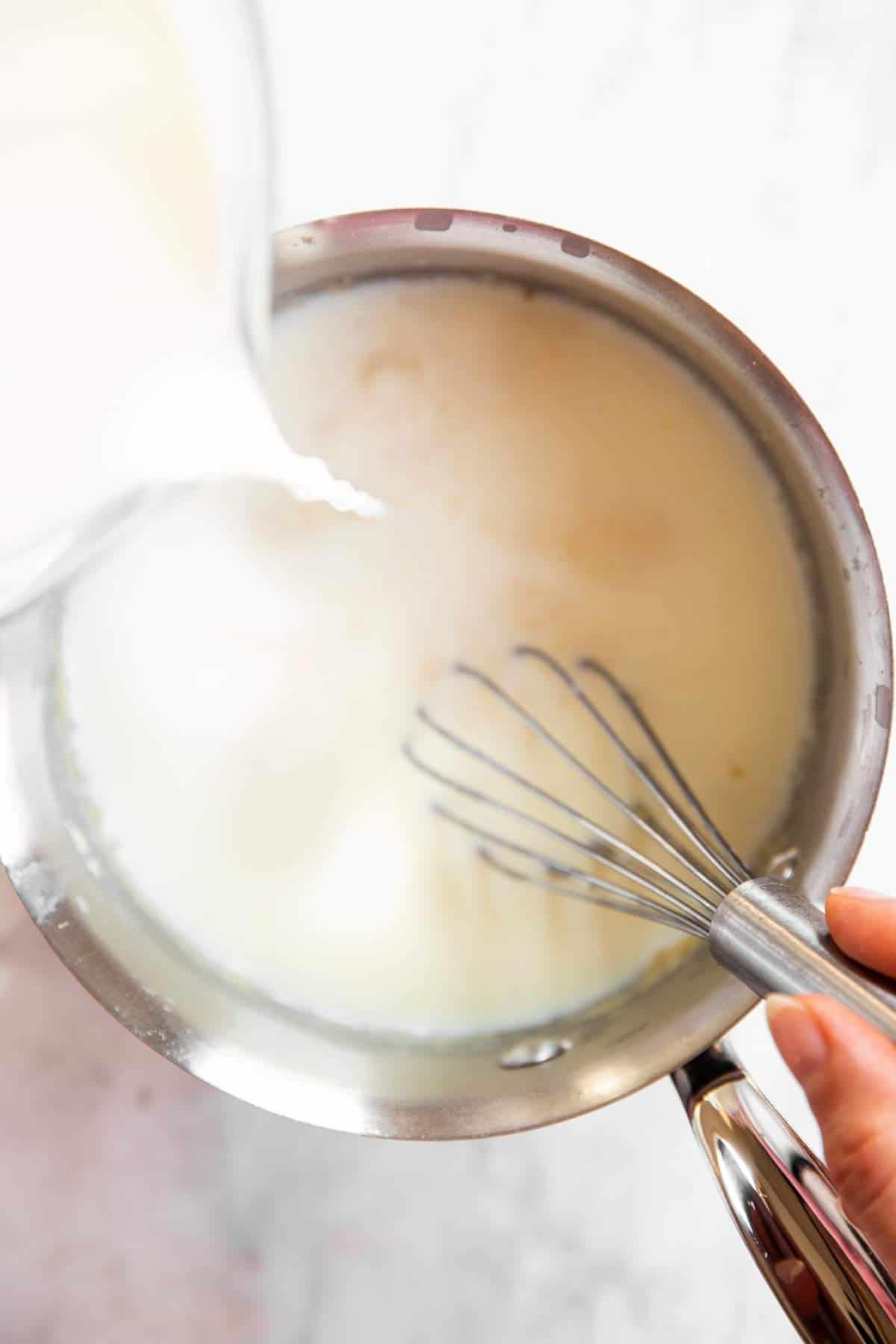 pouring milk into saucepan
