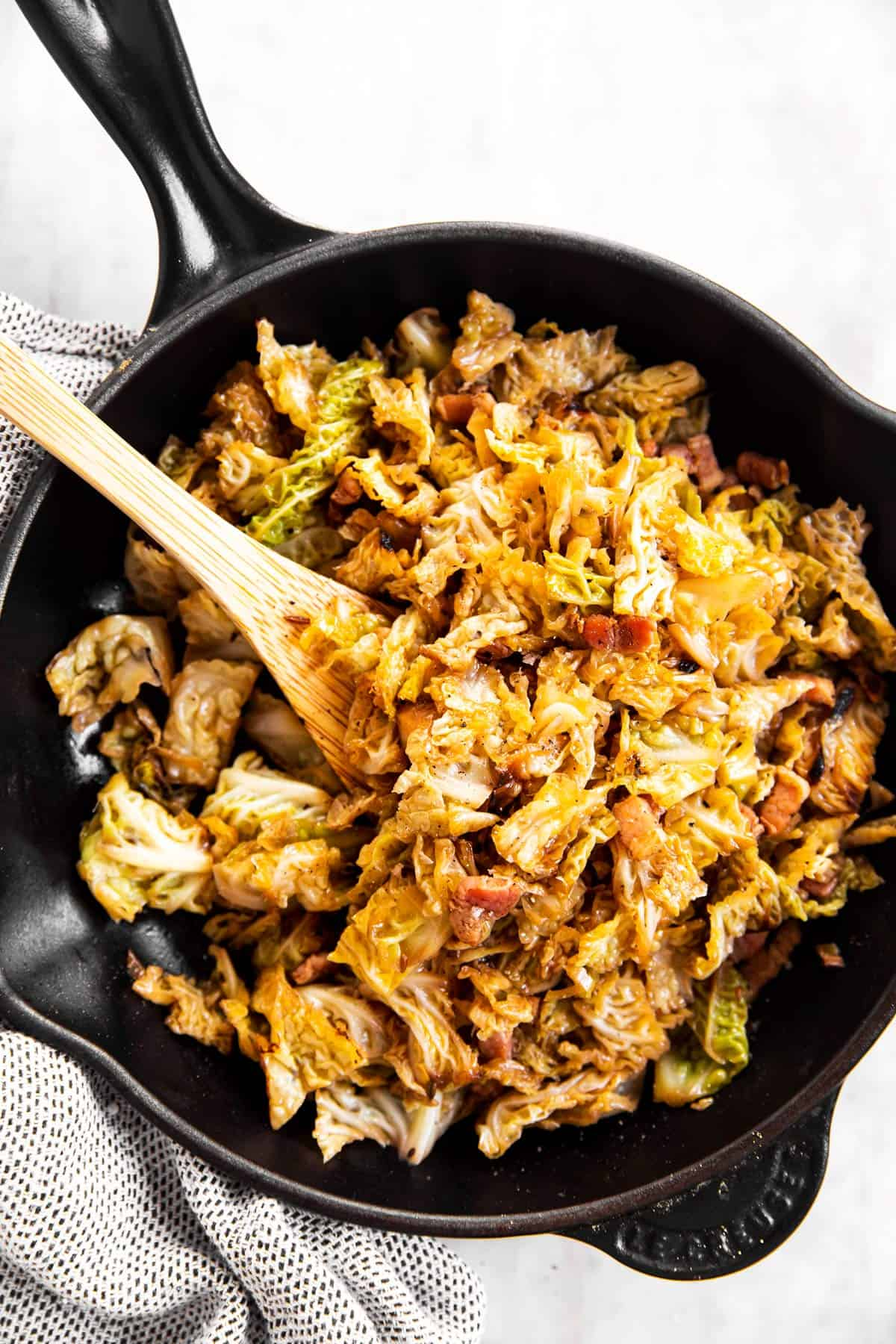 overhead view of black cast iron skillet with braised cabbage inside