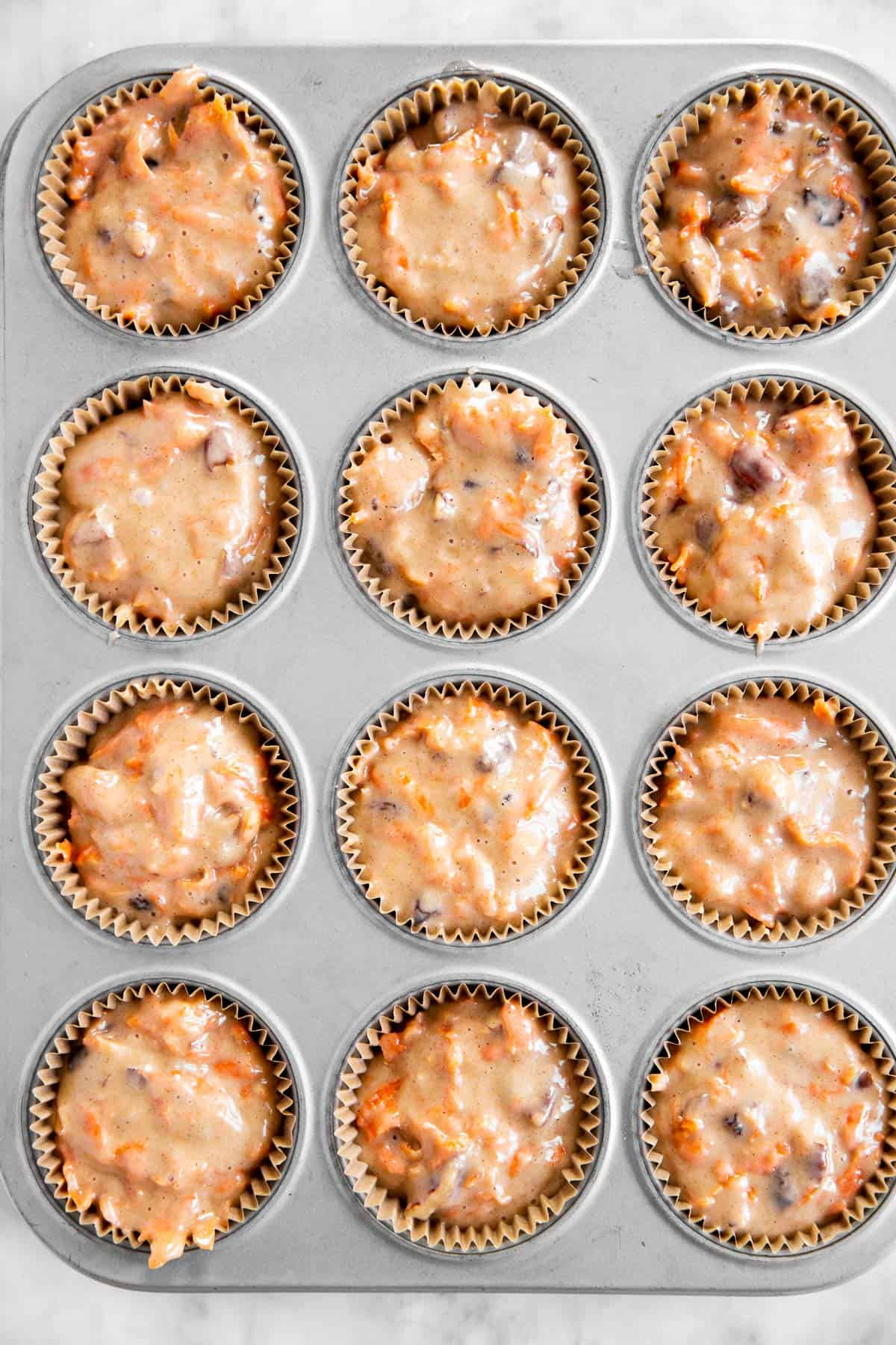 carrot muffin batter divided between 12 lined muffin cups