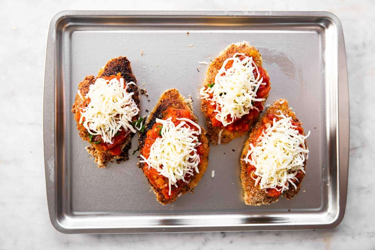 four breaded chicken breasts topped with marinara sauce, herbs and cheese on sheet pan