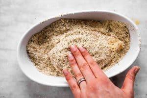 female hand pressing breadcrumbs on chicken breast