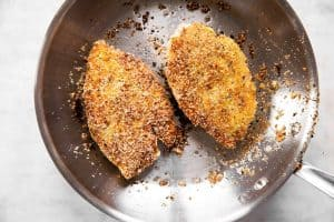 two breaded chicken breasts browned in skillet