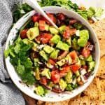 overhead image of white bowl filled with chunky avocado salsa