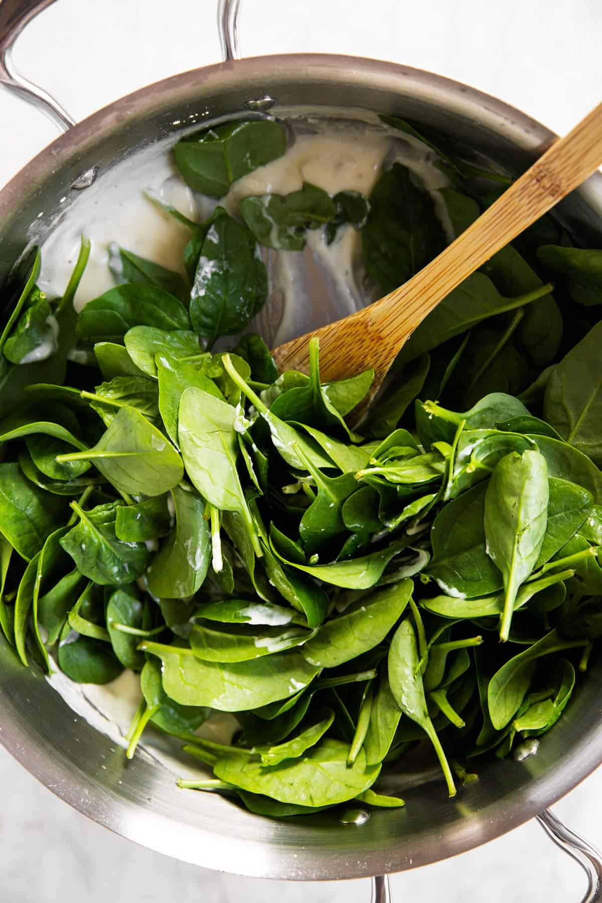 raw baby spinach in pan with Béchamel sauce