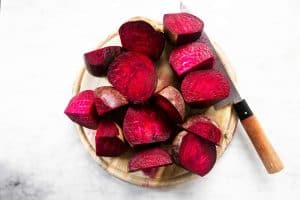 sliced beets on chopping board with knife
