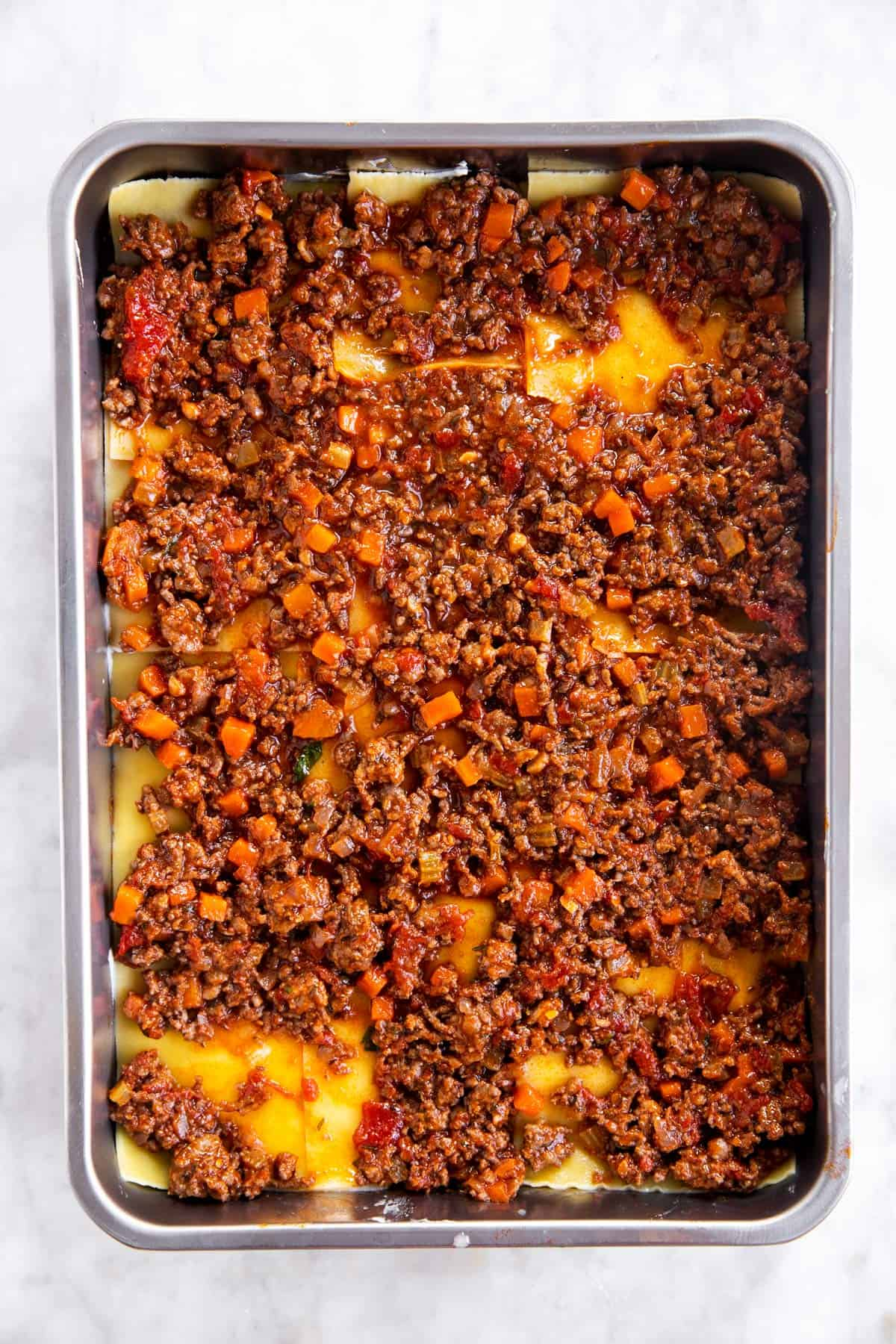 casserole dish with second layer of bolognese sauce