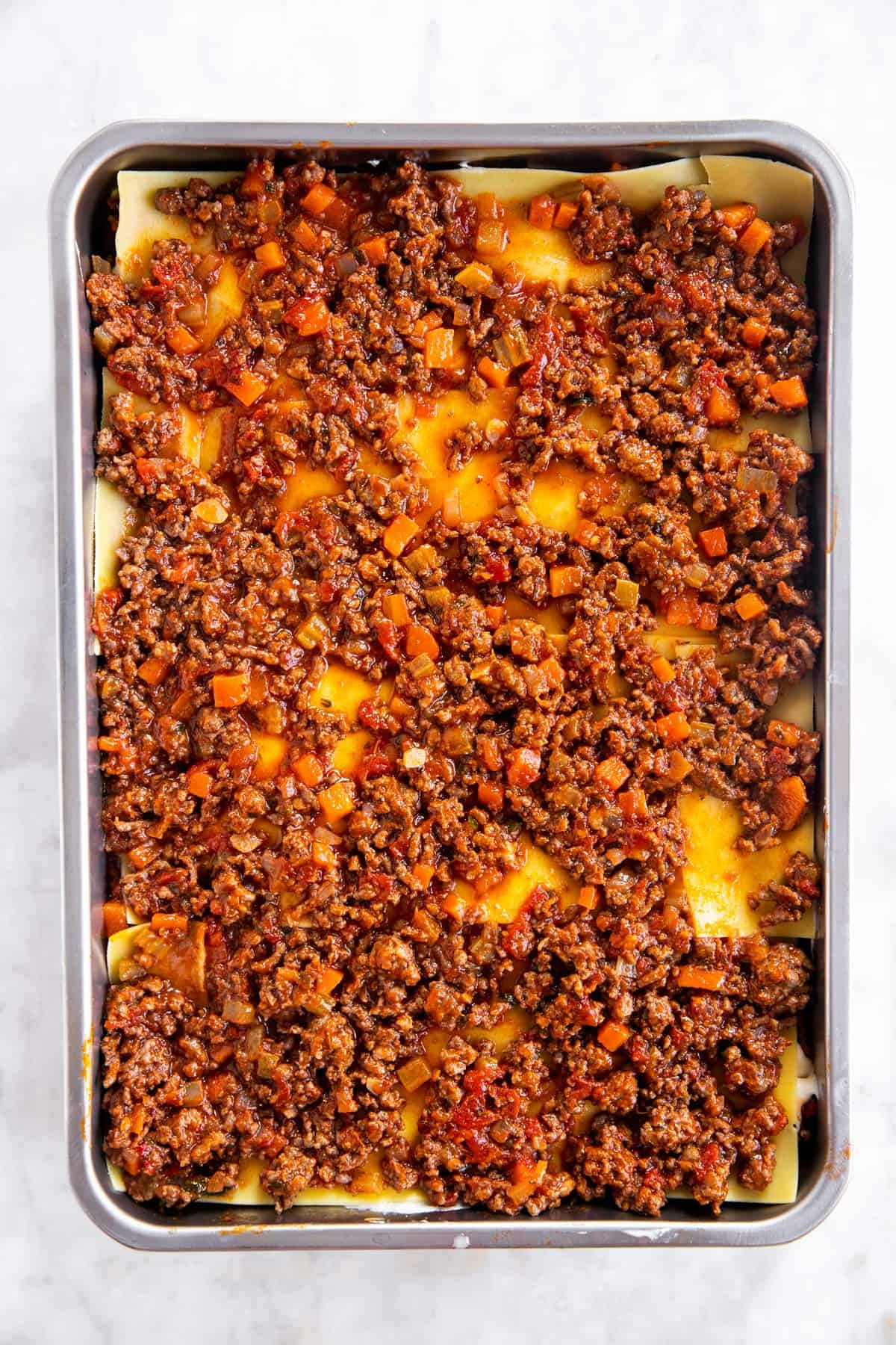 casserole dish with third layer of bolognese sauce