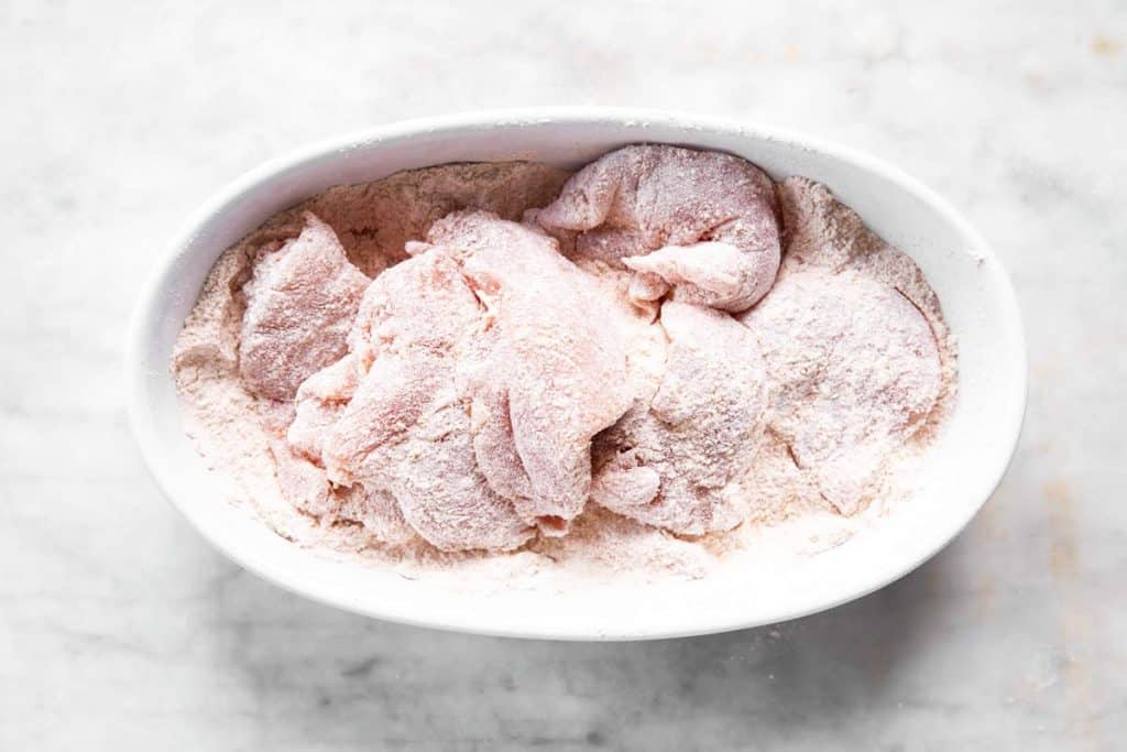 pile of chicken breast in white dish with flour