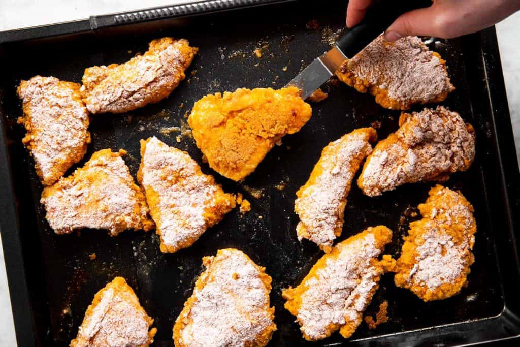 flipping oven fried chicken on black pan