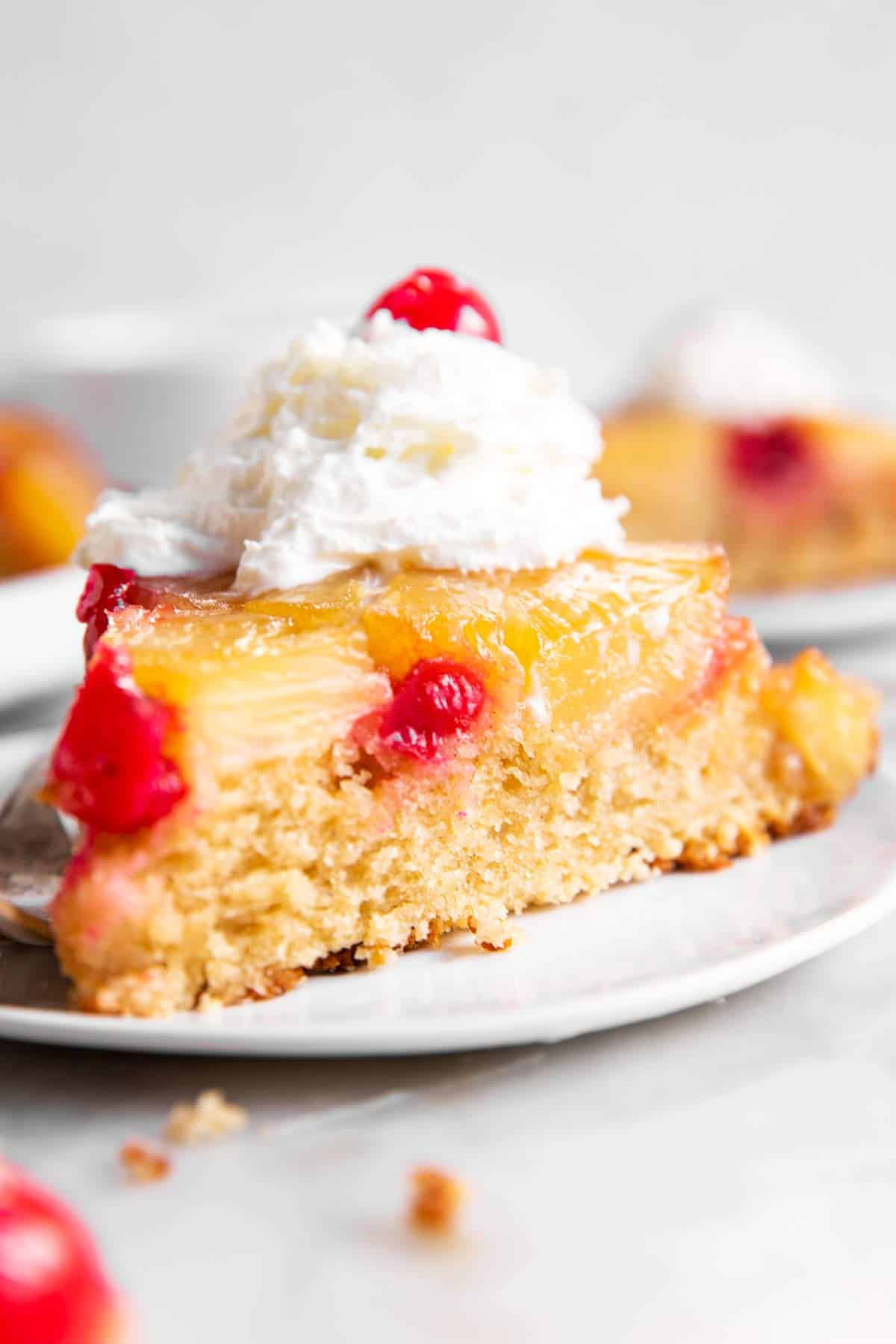 slice of pineapple upside down cake with whipped cream on white plate
