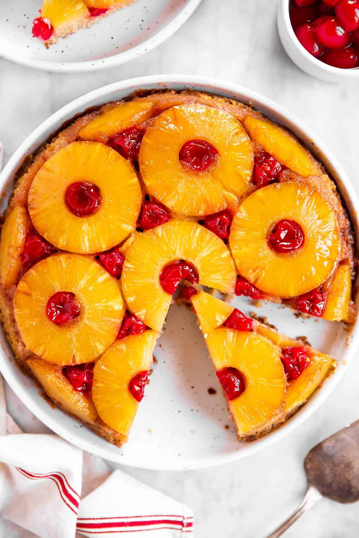 overhead view of sliced pineapple upside down cake on marble surface