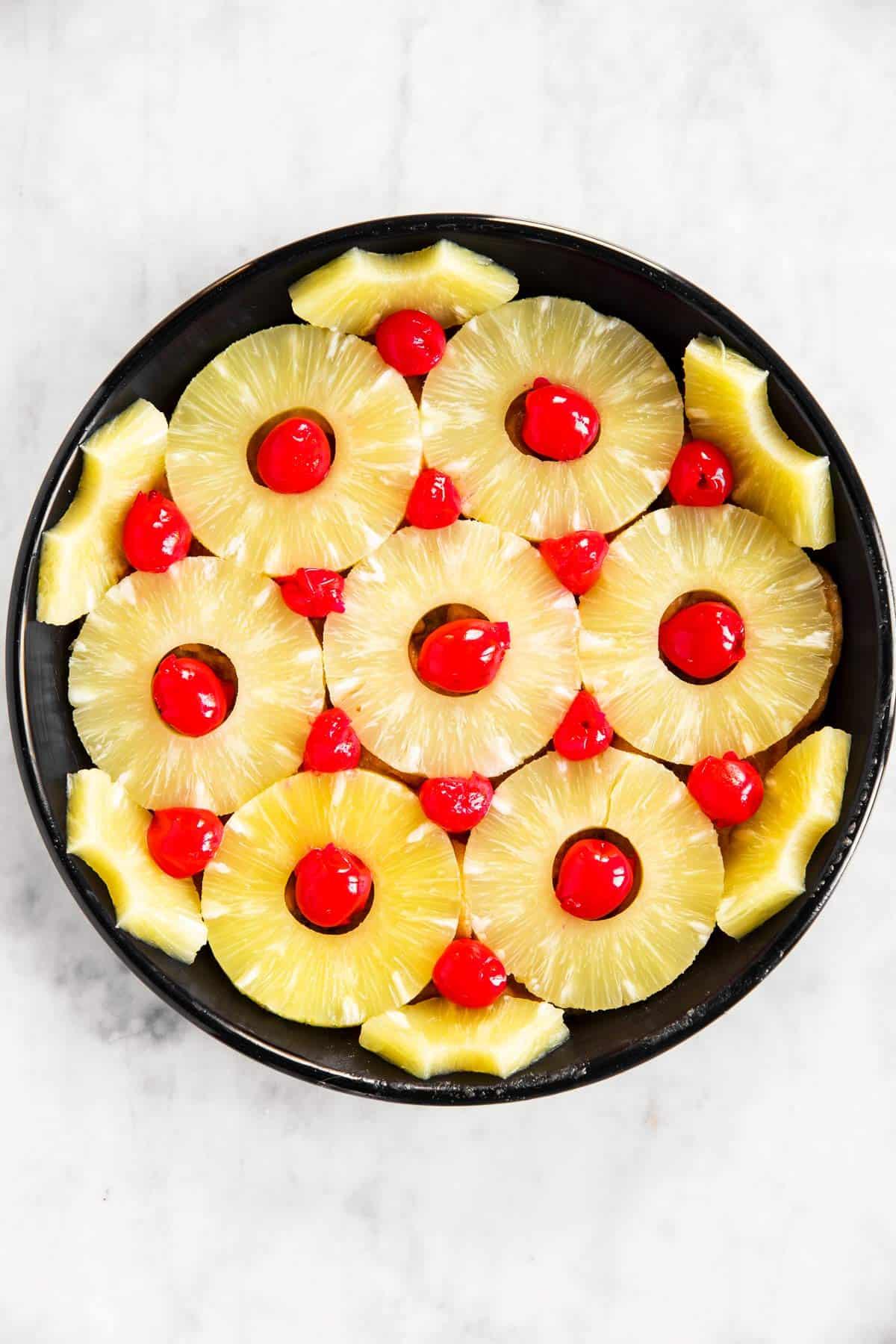 black cake pan lined with pineapple rings and maraschino cherries