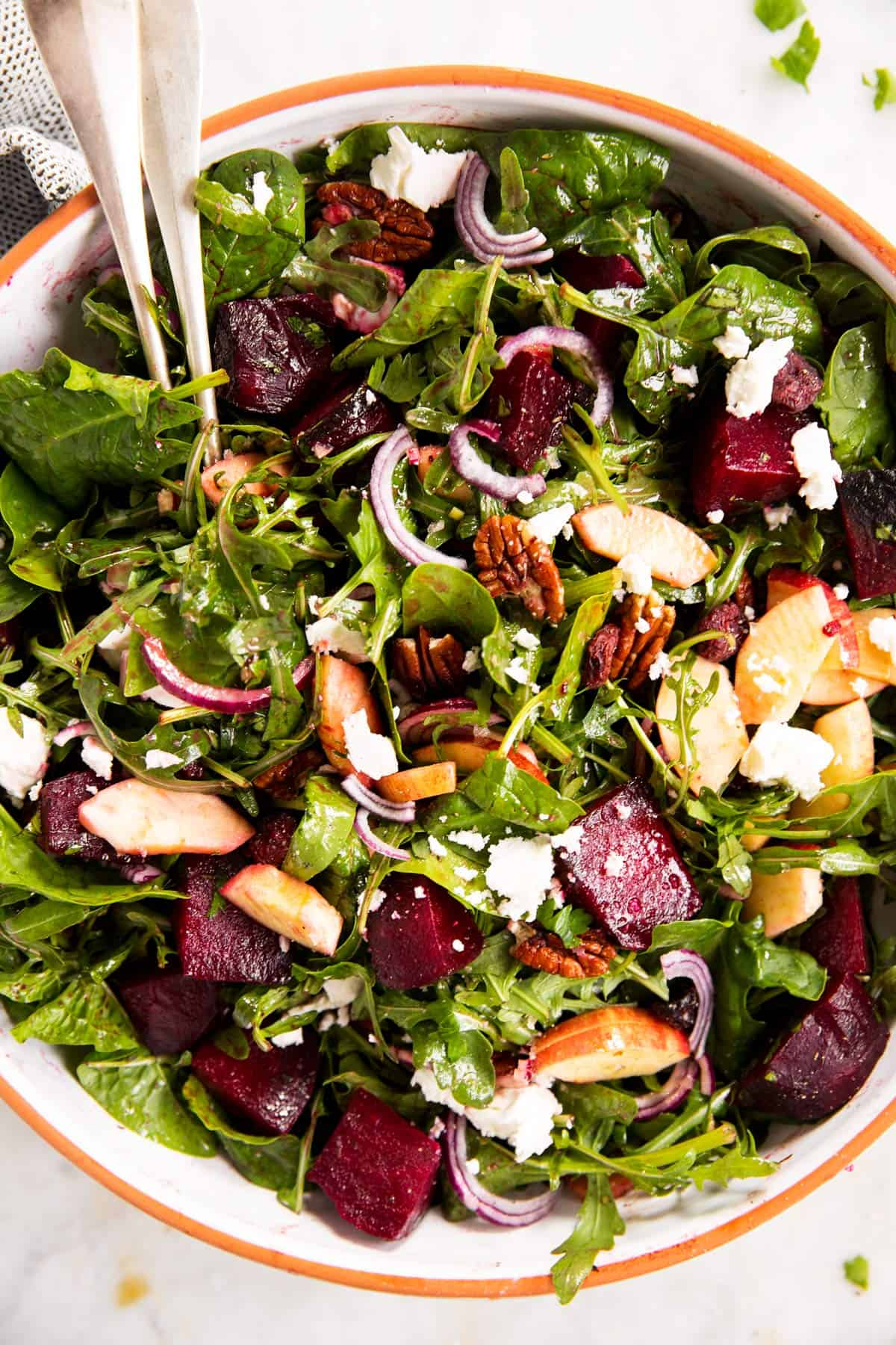 overhead close up photo of roasted beet salad with goat's cheese in large salad bowl
