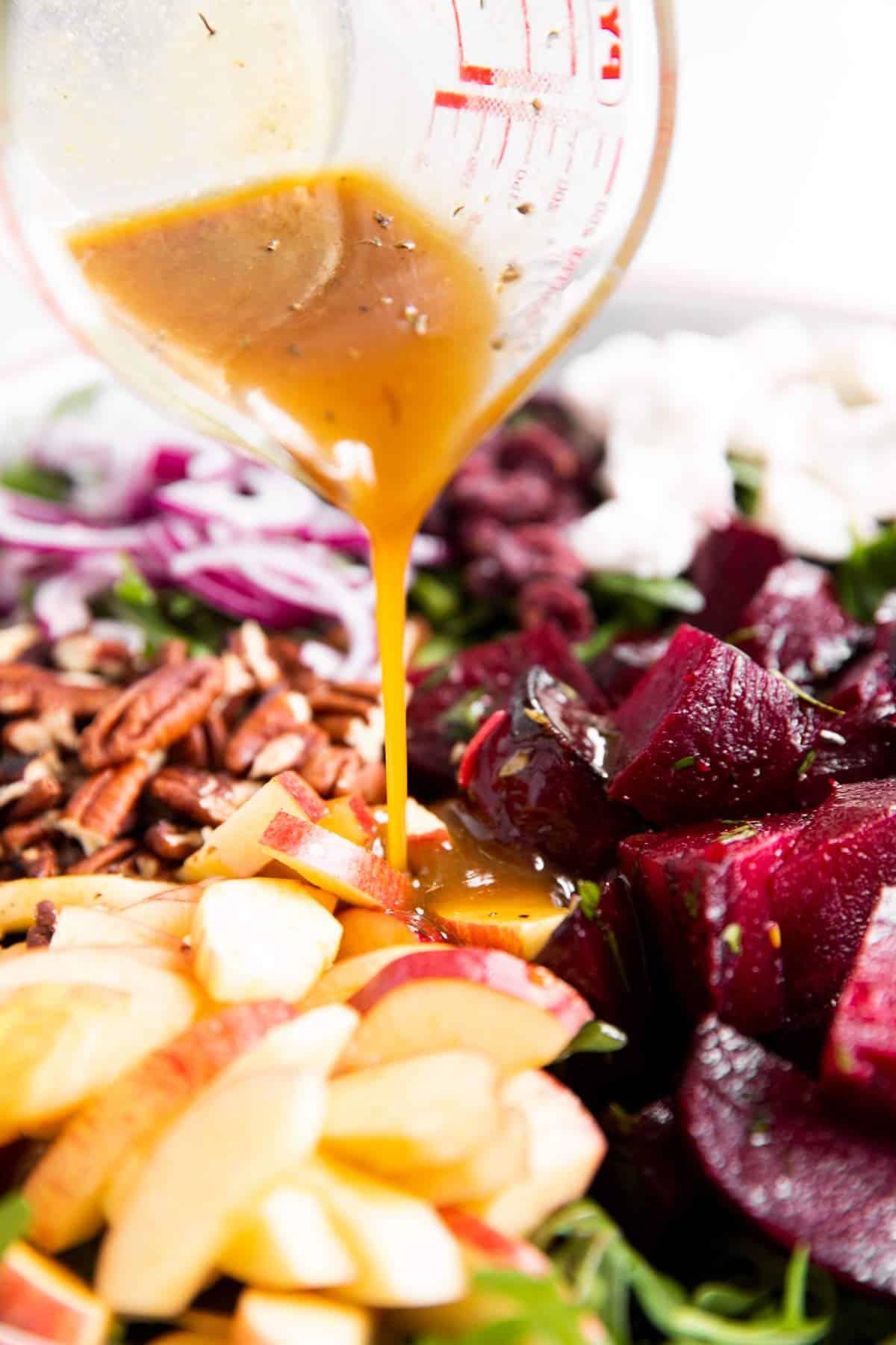 pouring salad dressing over ingredients for roasted beet salad