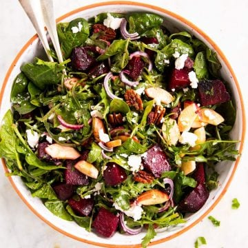 overhead photo of roasted beet salad with goat's cheese in large salad bowl
