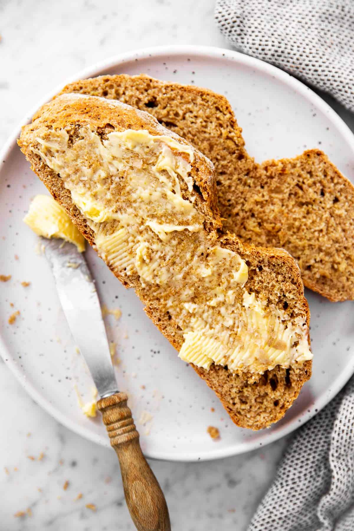two slices of soda bread on white plate, one slice is buttered the other is plain