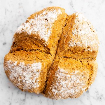 overhead view of baked Irish soda bread on marble surface