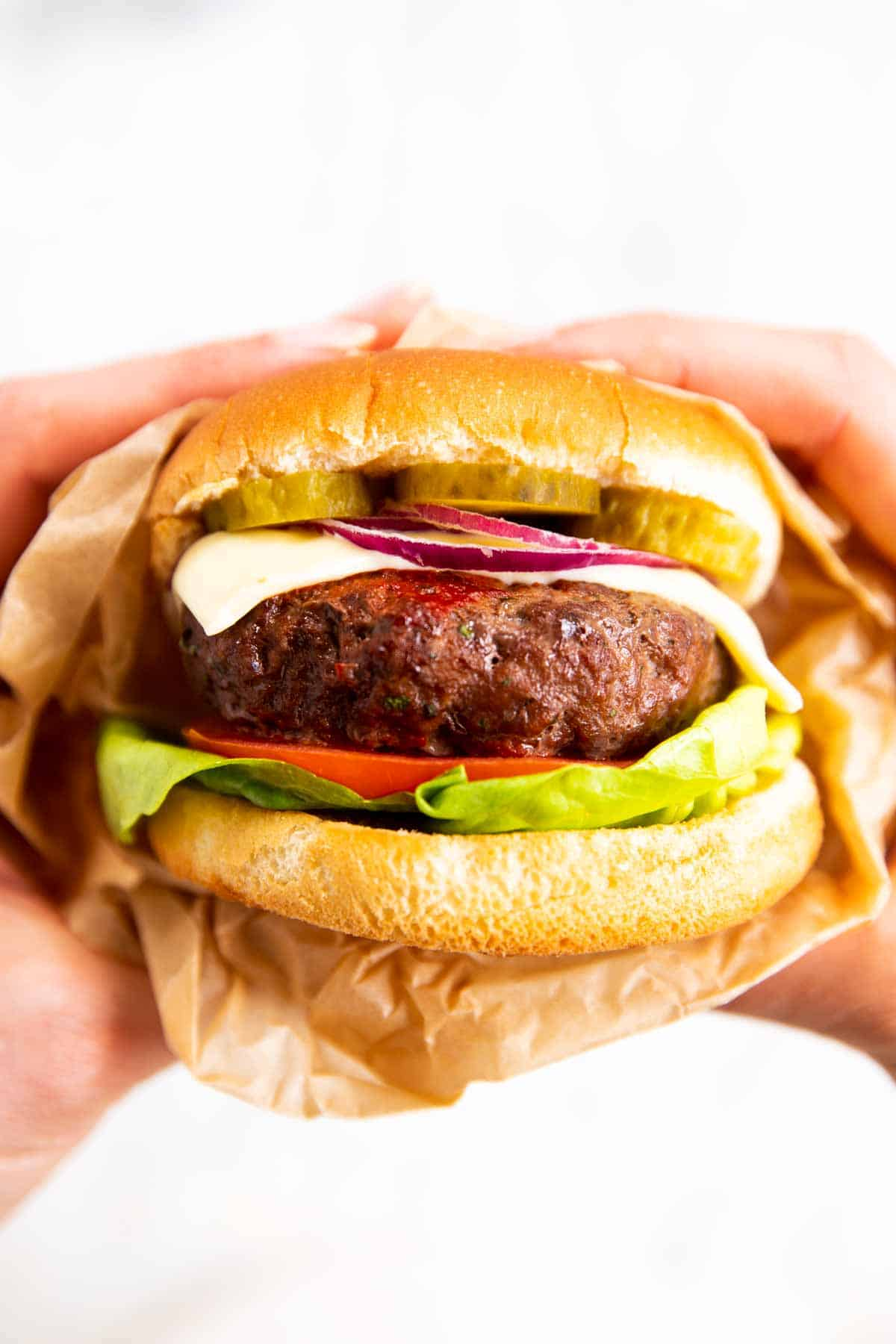 female hands holding burger with air fried patty
