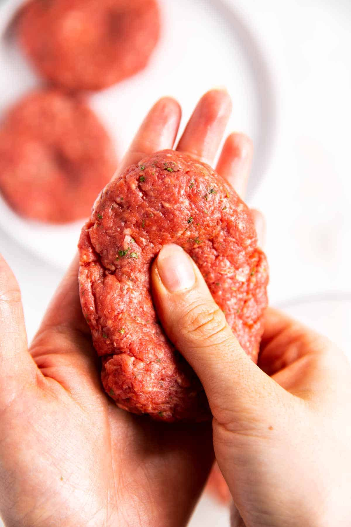 female hands shaping burger patty