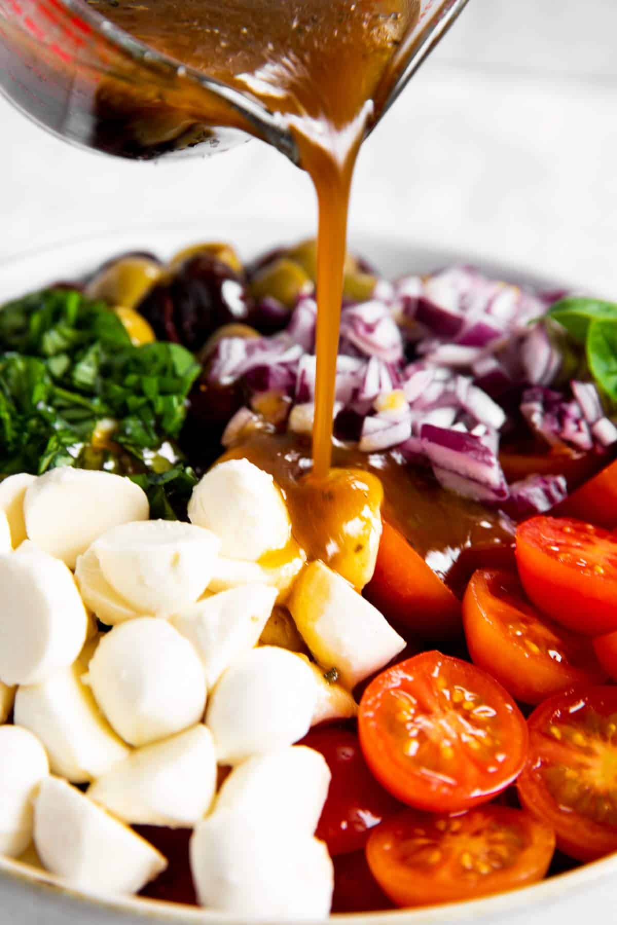 pouring balsamic vinaigrette dressing over ingredients for cherry tomato salad
