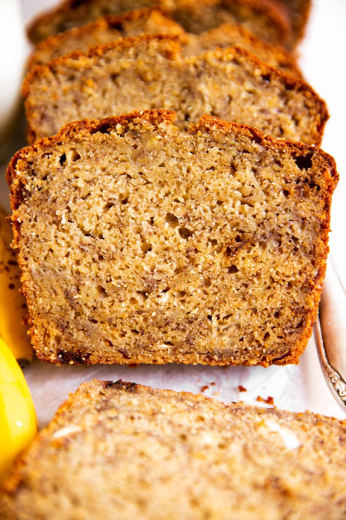 frontal view of sliced banana bread on white parchment paper