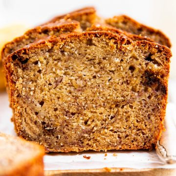 frontal view of sliced banana bread on parchment paper sitting on wooden board