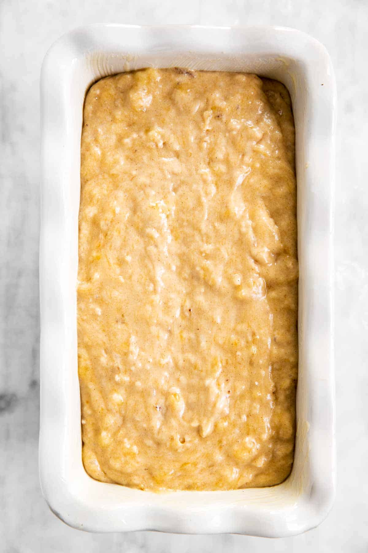 banana bread batter in white ceramic loaf pan sitting on marble surface
