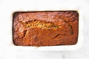 baked banana bread in white ceramic loaf pan sitting on marble surface