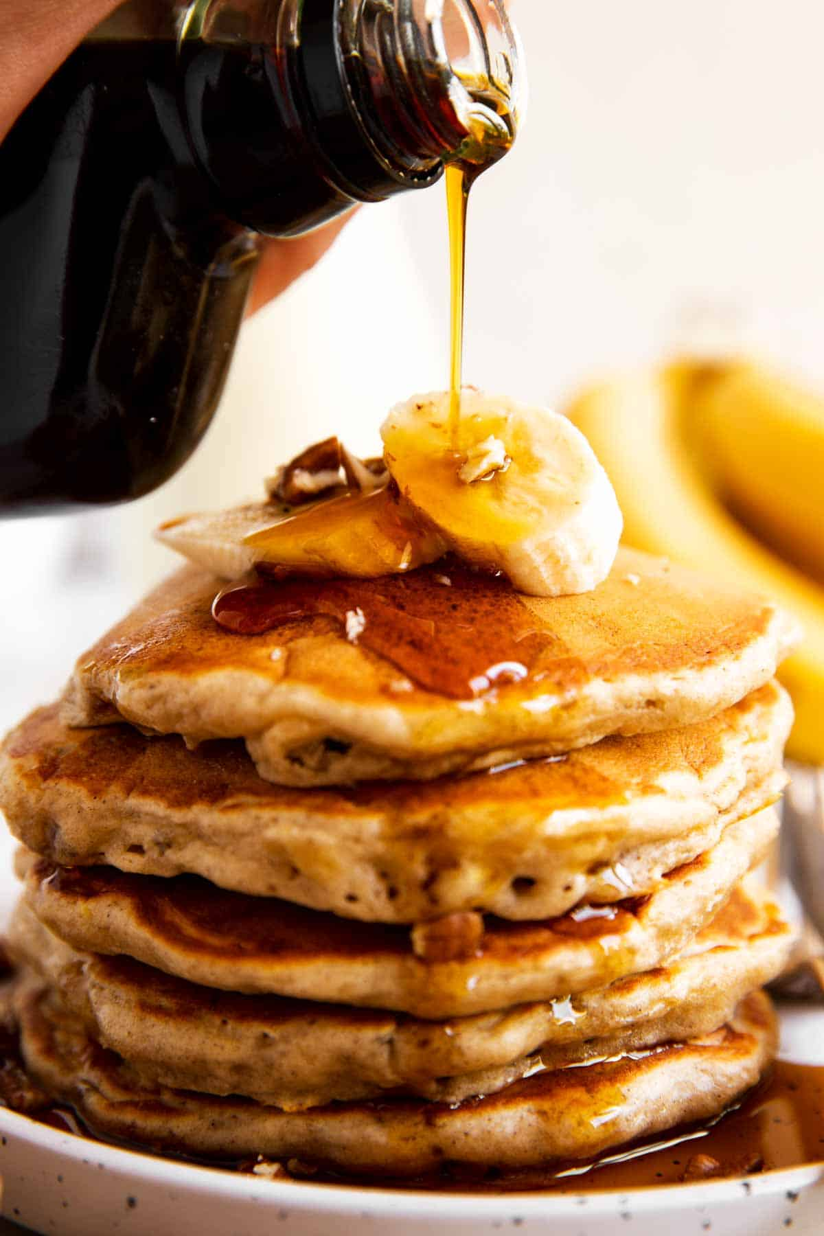 maple syrup pouring over stack of banana pancakes