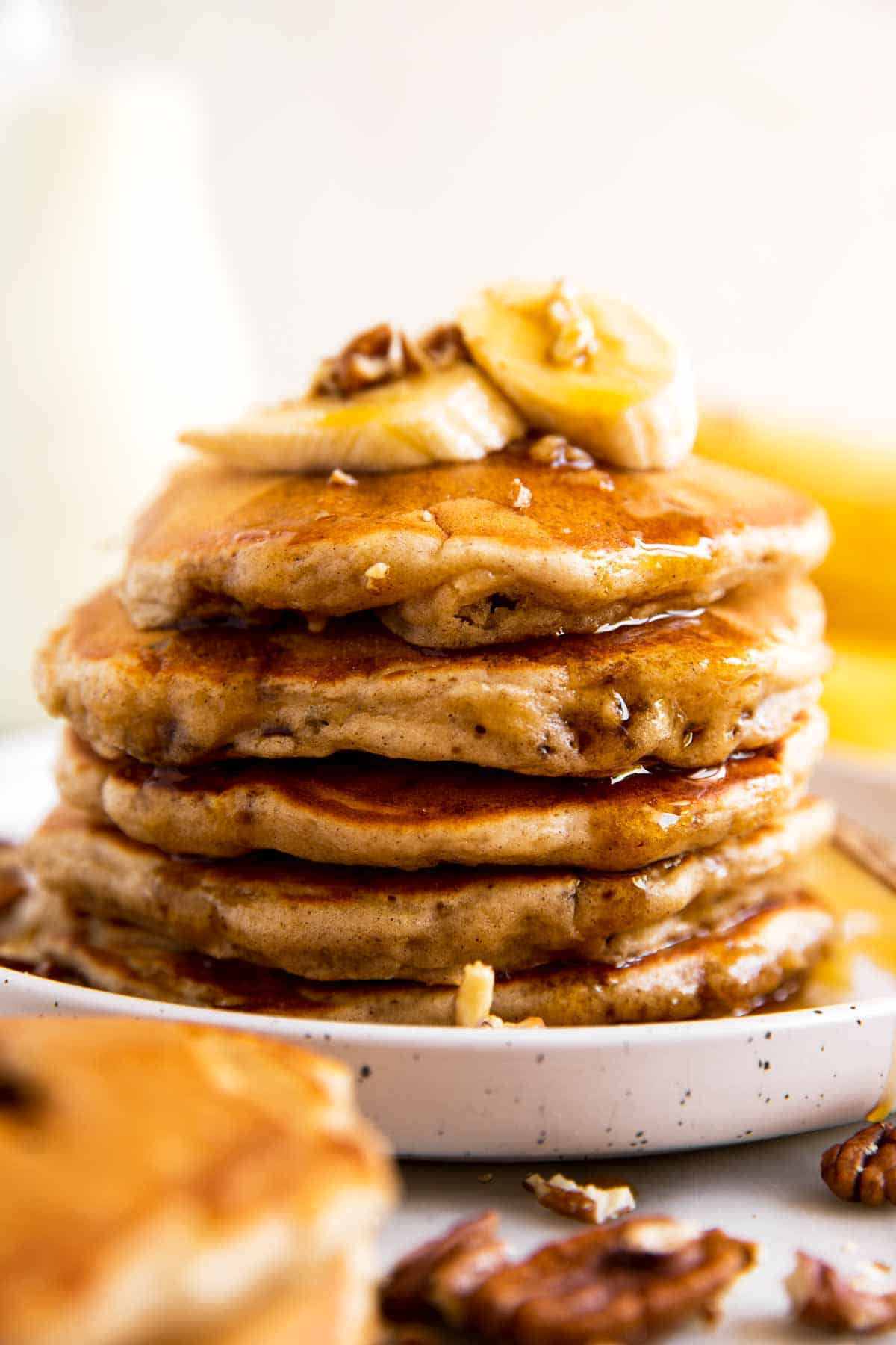 stack of banana pancakes on white plate with maple syrup, banana slices and pecans