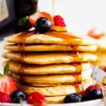 maple syrup pouring over stack of buttermilk pancakes with berries