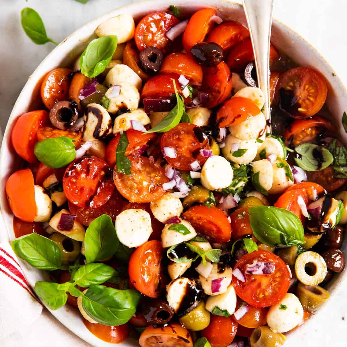 overhead view of white bowl filled with cherry tomato salad
