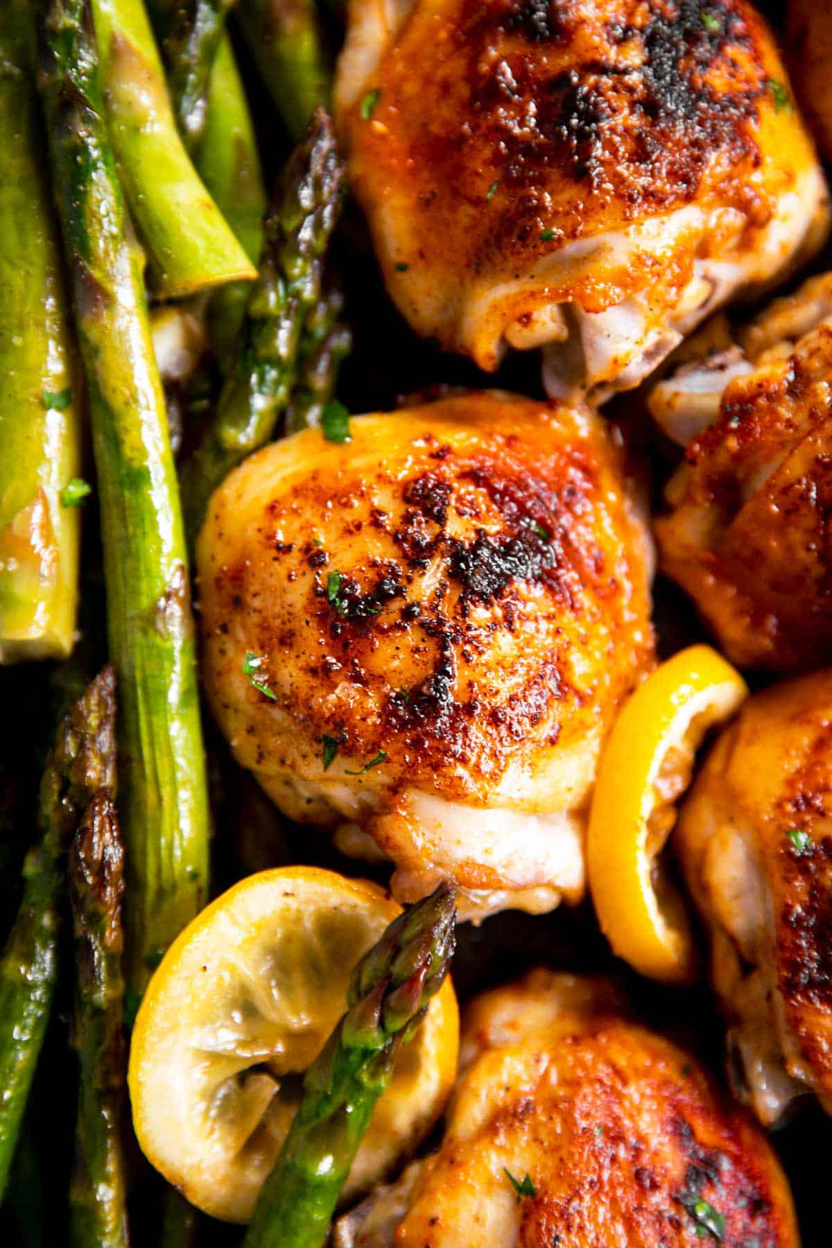 close up photo of chicken thighs and asparagus roasted with lemon