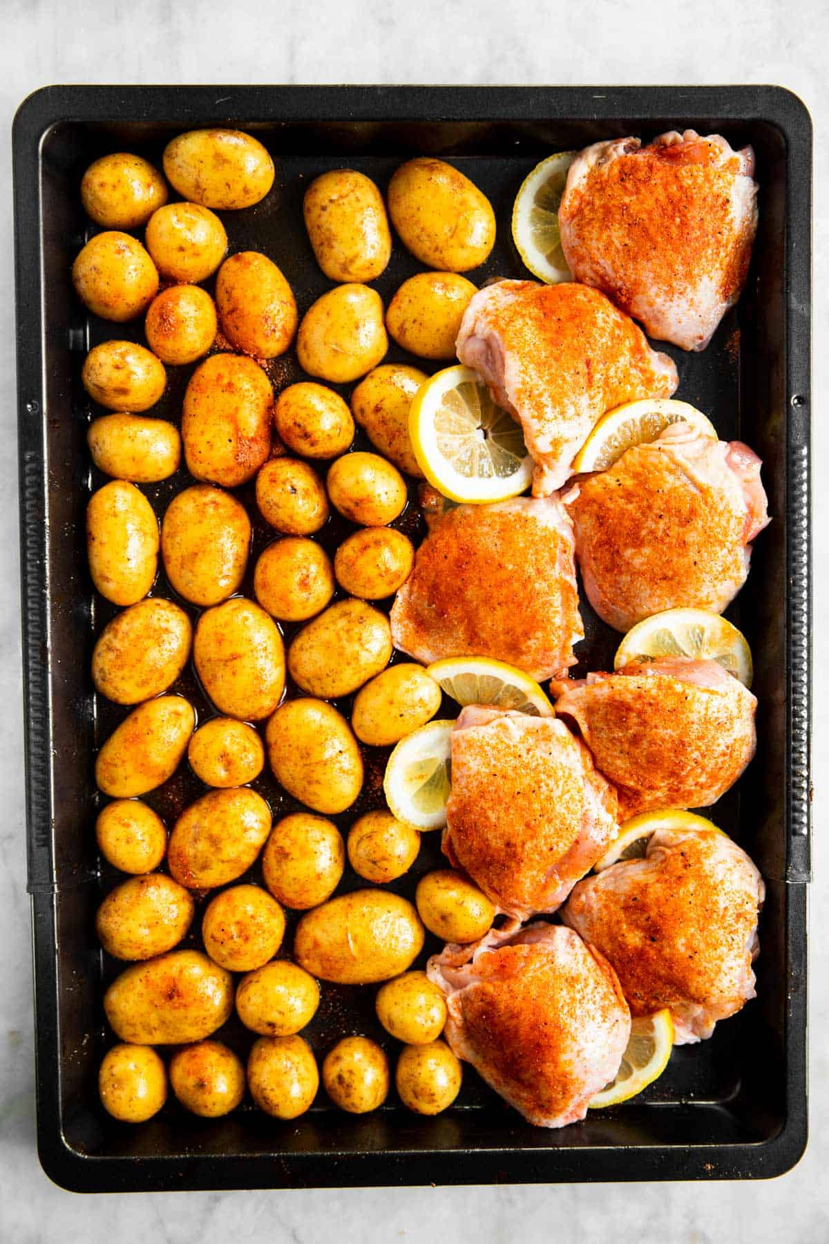 overhead view of seasoned potatoes and chicken thighs with lemon slices on black sheet pan