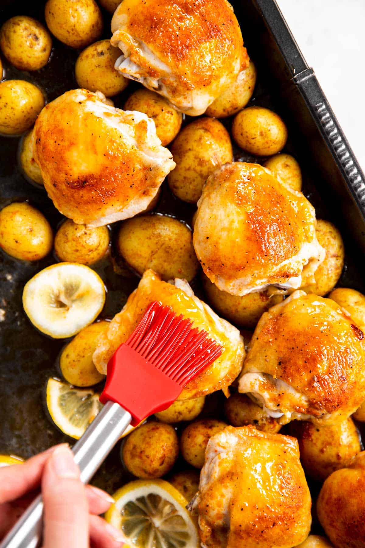 basting chicken thighs with red pastry brush
