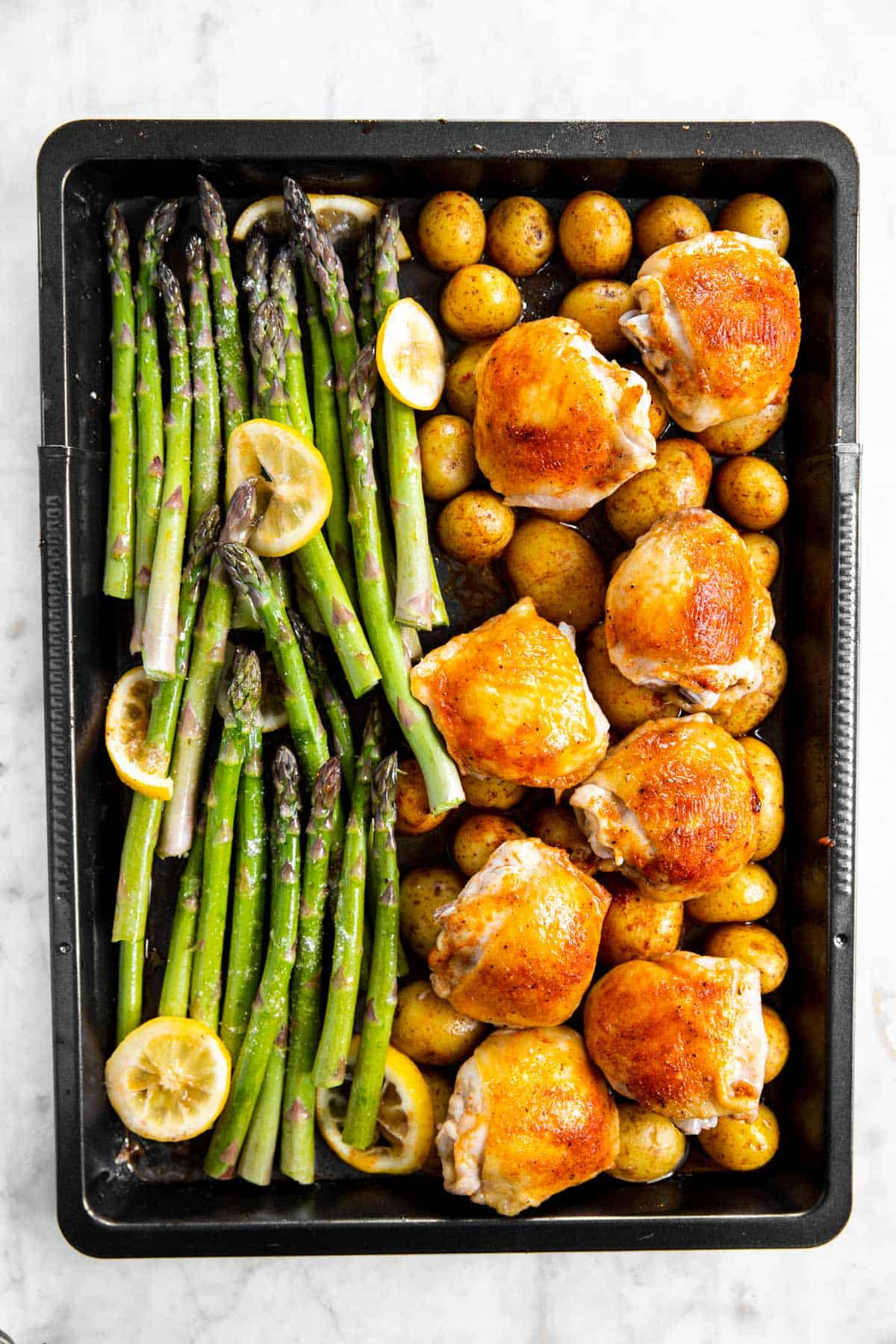 overhead view of half-roasted potatoes and chicken thighs with raw asparagus on black sheet pan