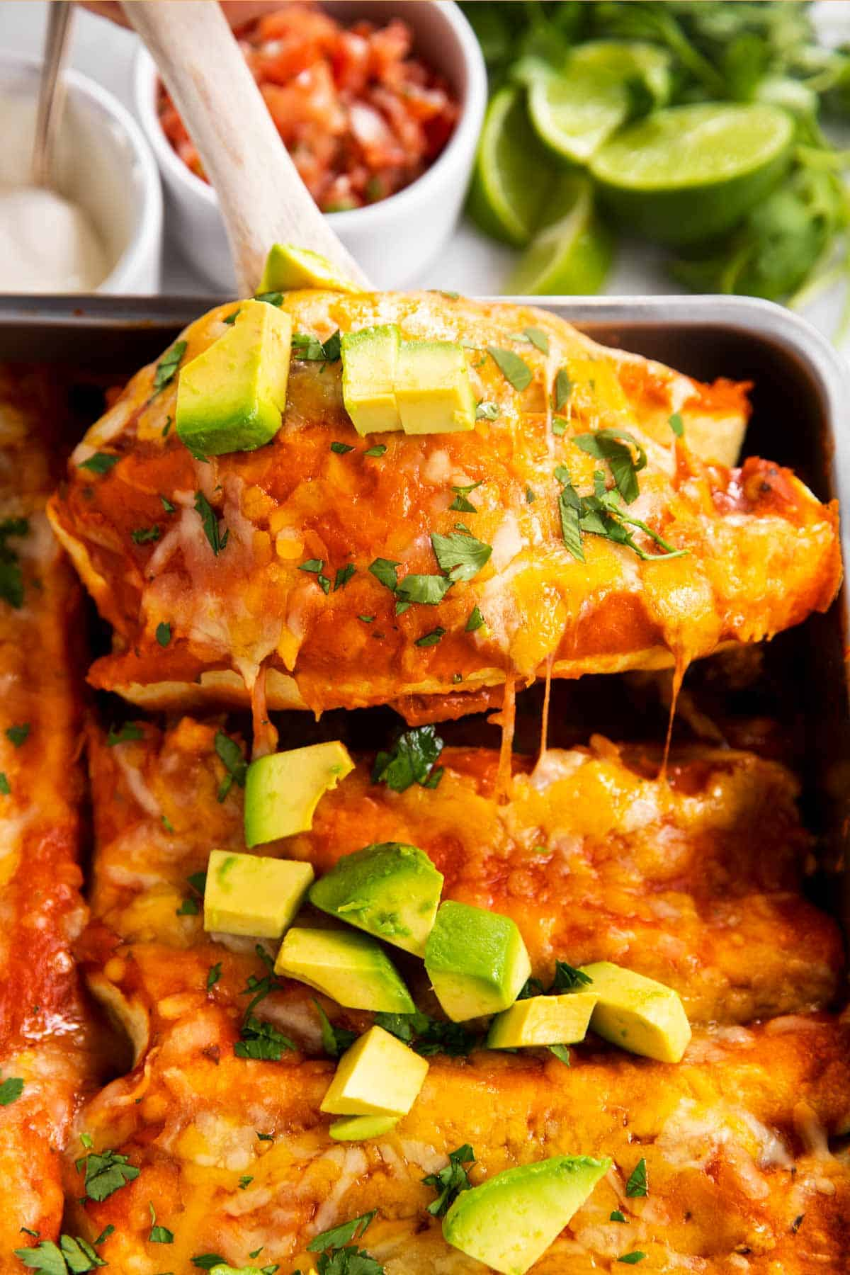lifting two chicken enchiladas out of casserole dish with wooden spoon