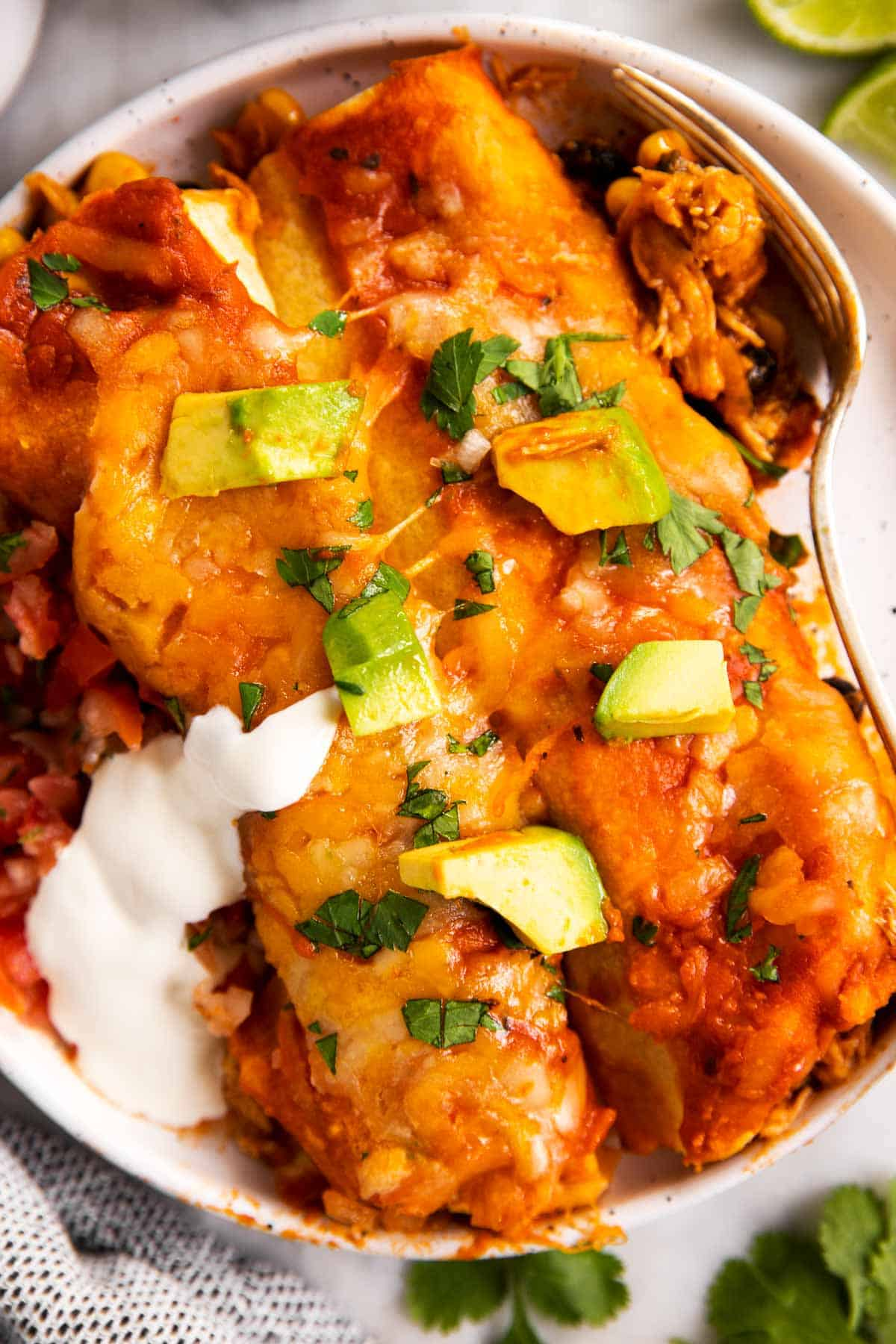 overhead view of two chicken enchiladas on white plate with avocado and sour cream