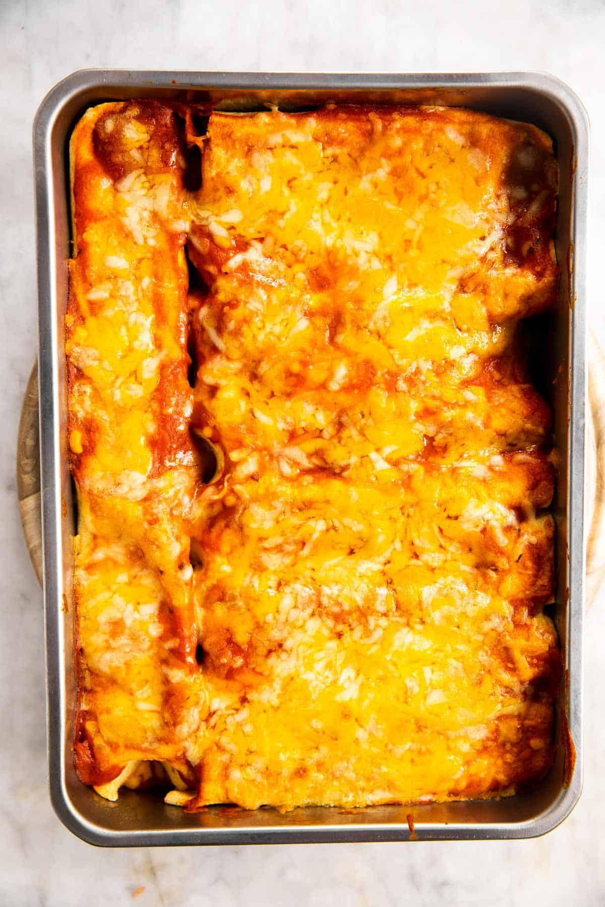baked chicken enchiladas in casserole dish