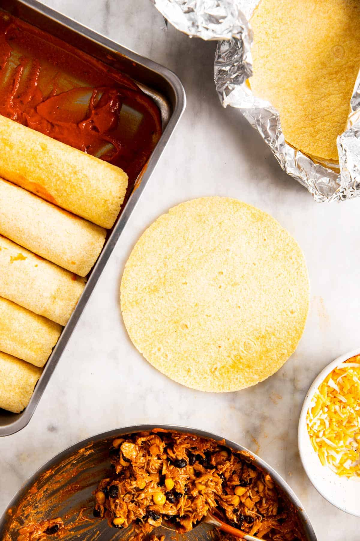 ingredients to assemble chicken enchiladas on marble surface