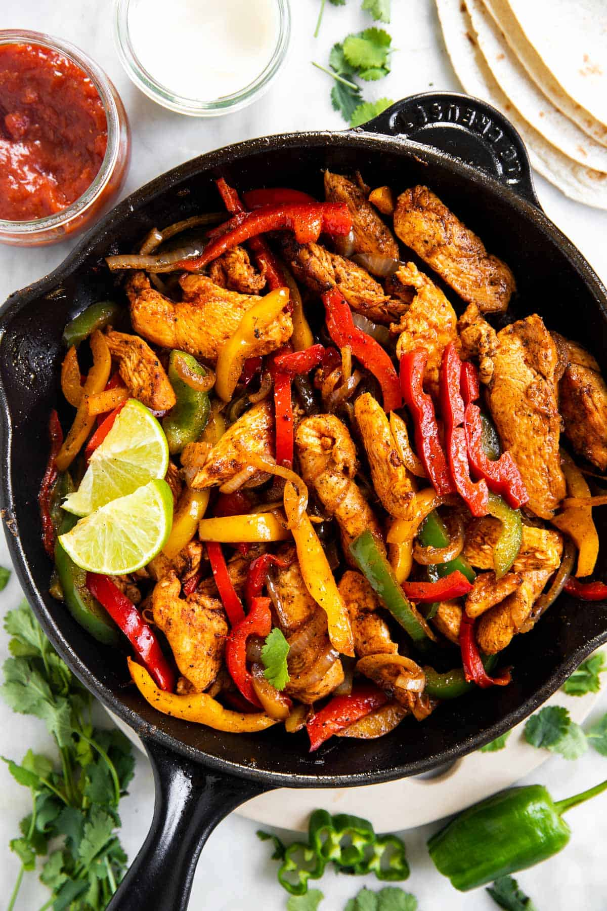 overhead view of chicken fajita filling in black cast iron skillet, surrounded by fajita toppings