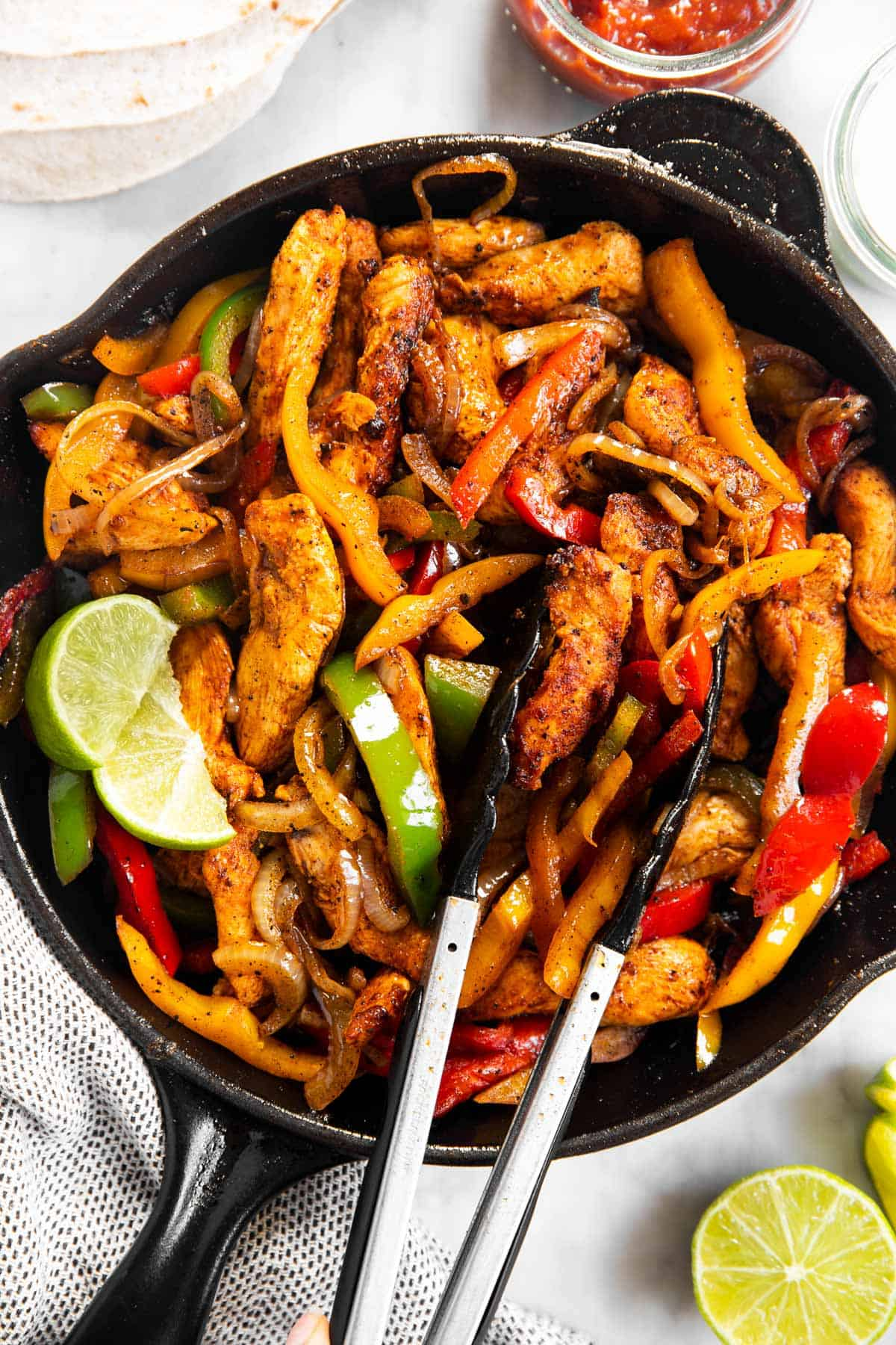 chicken fajita filling in black skillet with kitchen tongs surrounded by fajita toppings and wraps