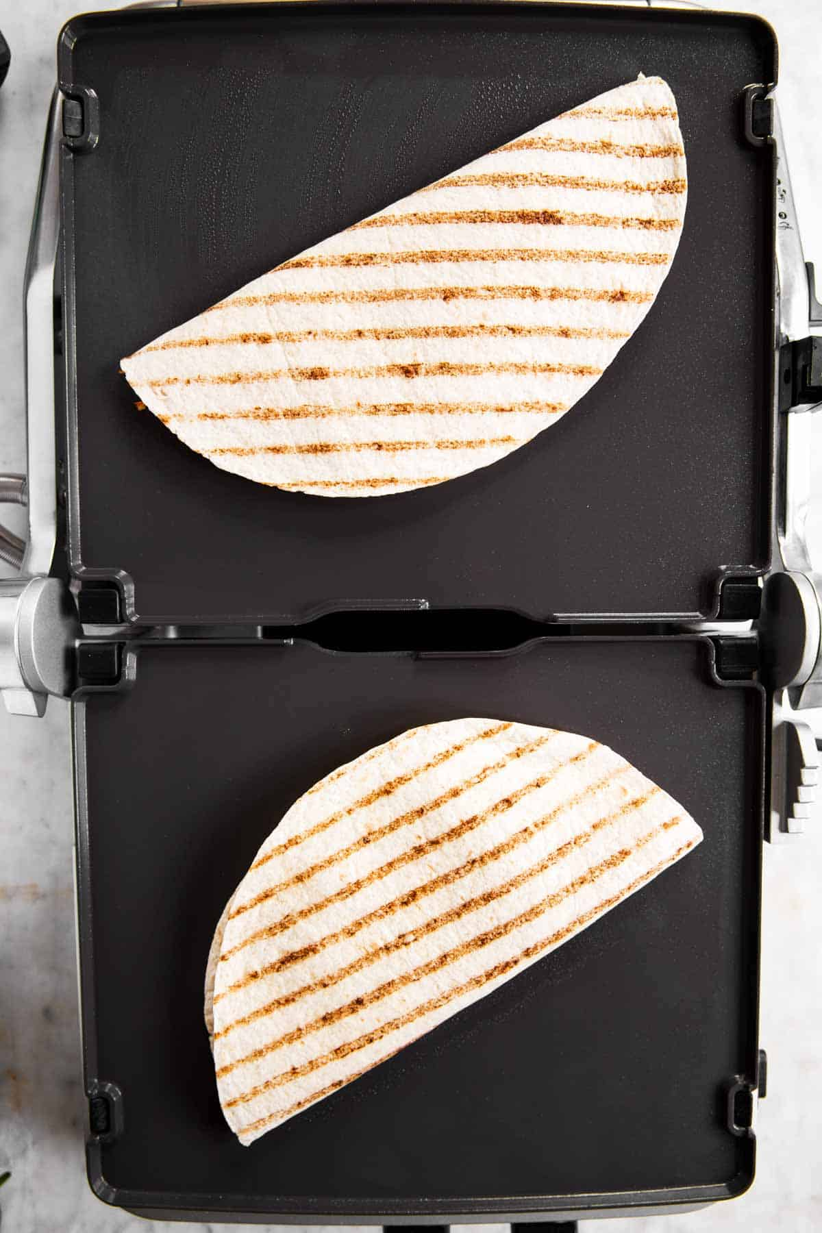 griddle with two quesadillas cooking