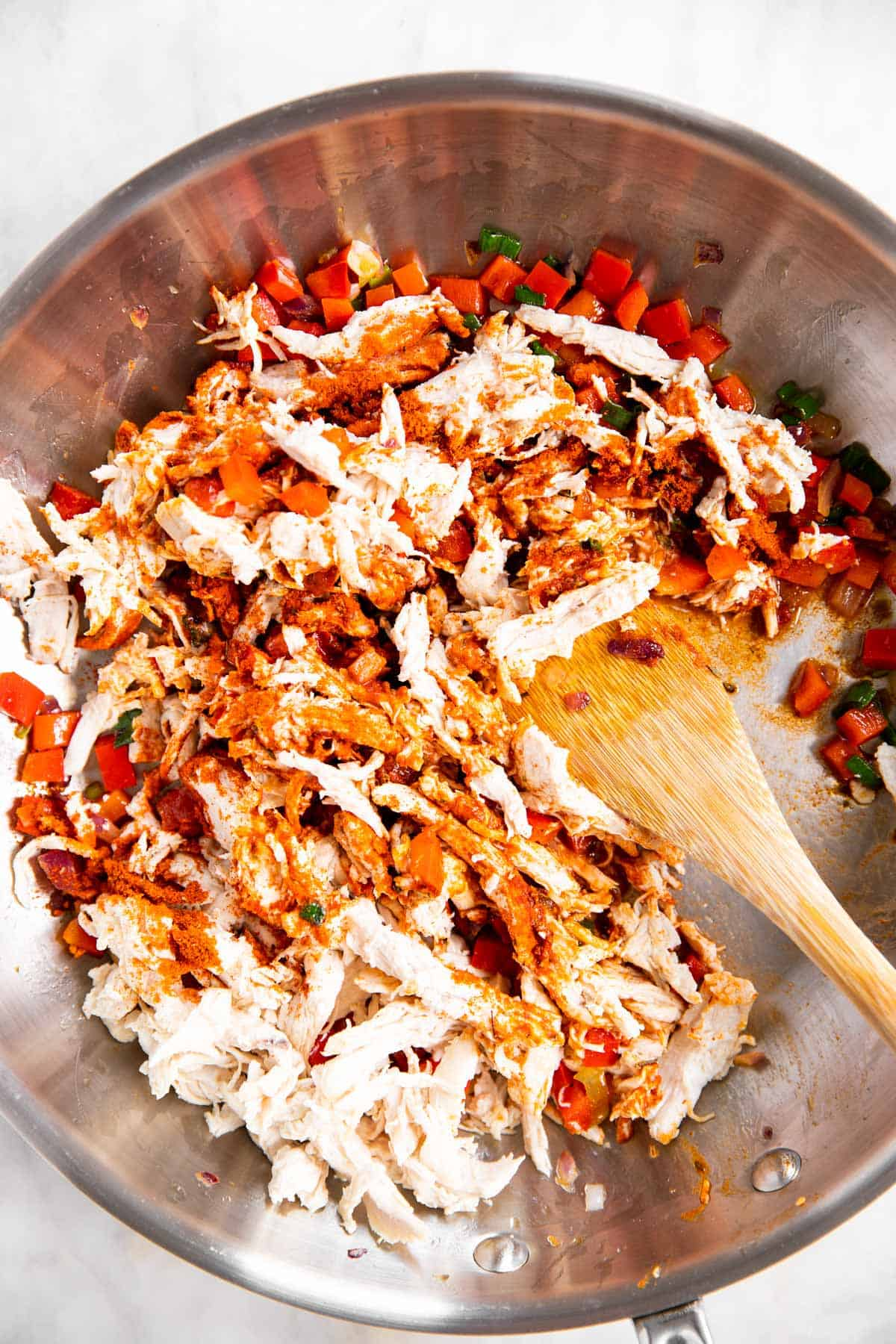 shredded chicken and seasoning being stirred into cooked onion and pepper mixture in skillet