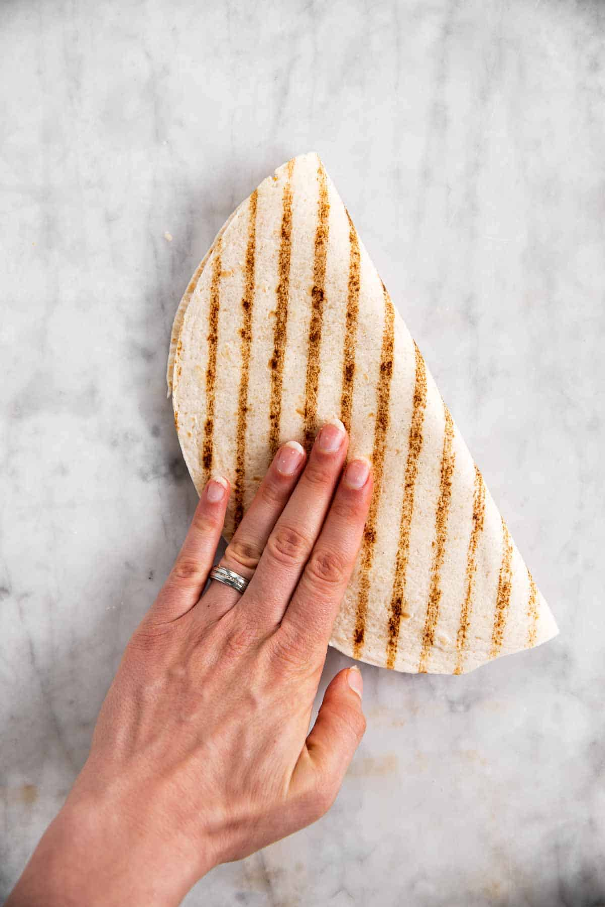 female hand folding tortilla wrap in half