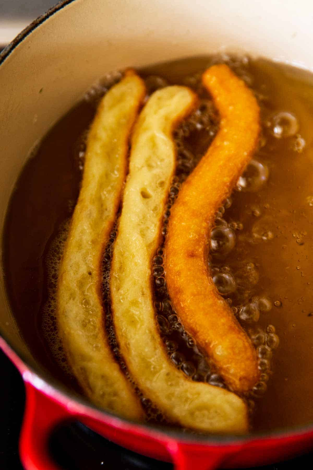 two unflipped churros and one flipped churro in simmering oil