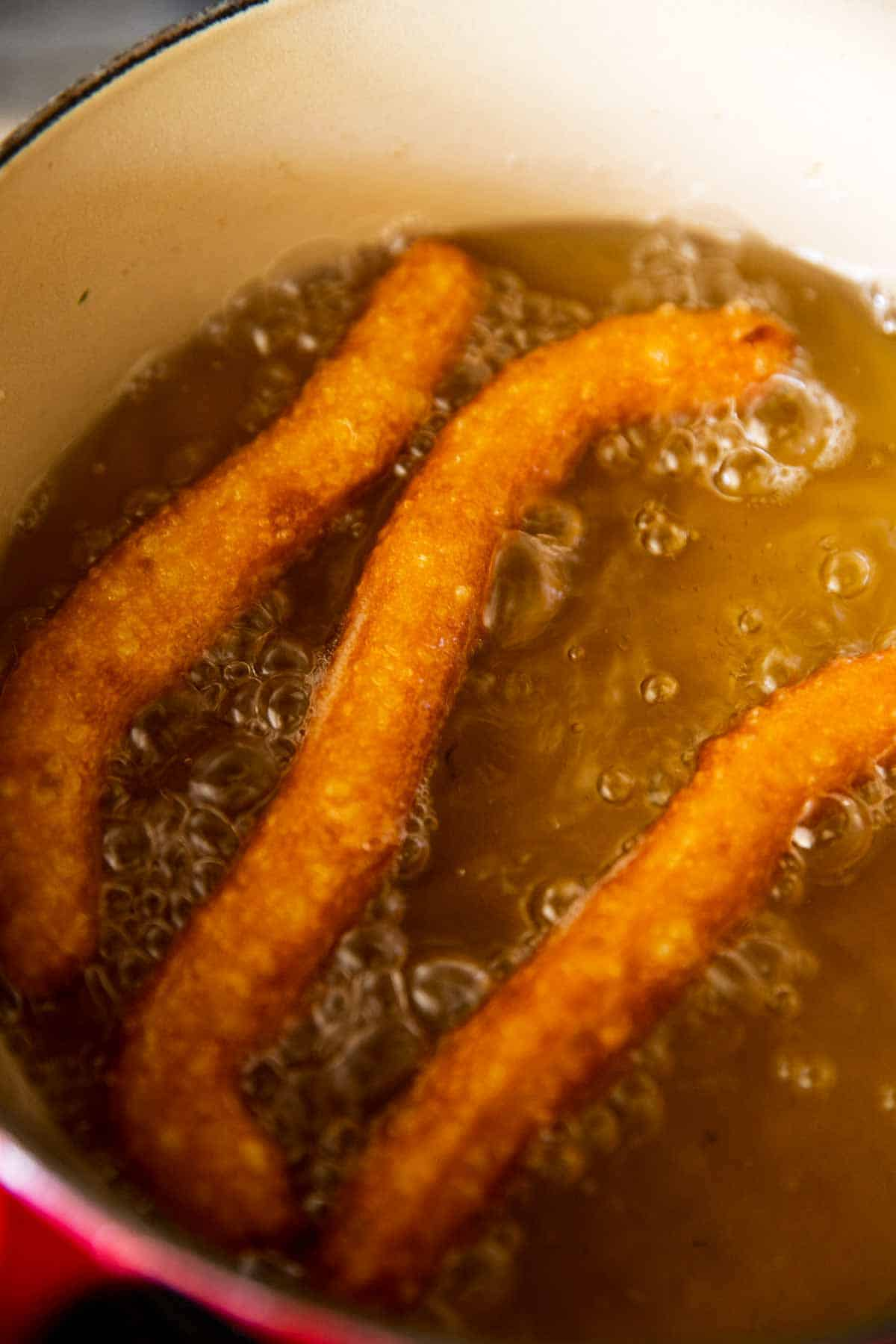 three flipped churros in simmering oil