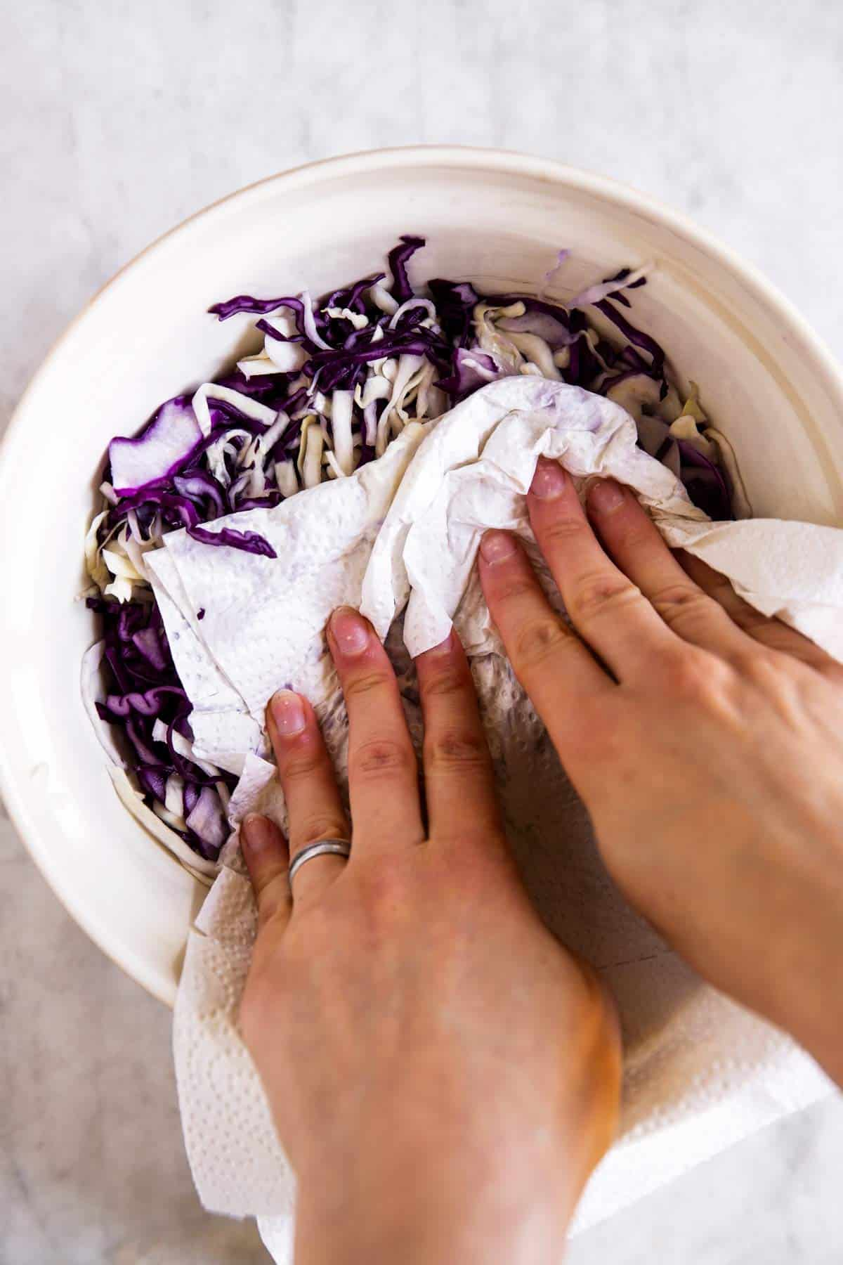 female hands patting dry cabbage in large mixing bowl
