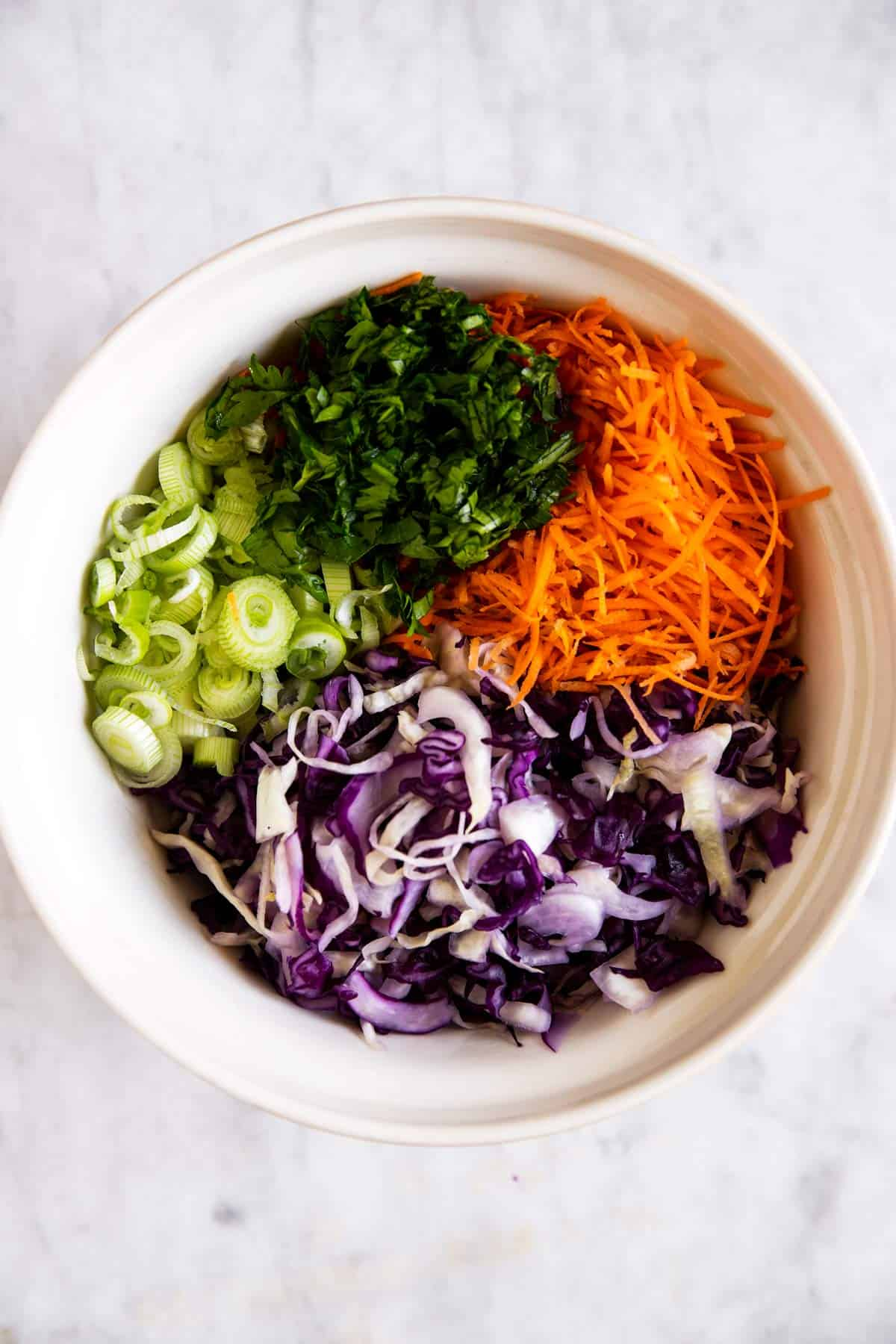 salad ingredients for cilantro lime slaw in salad bowl