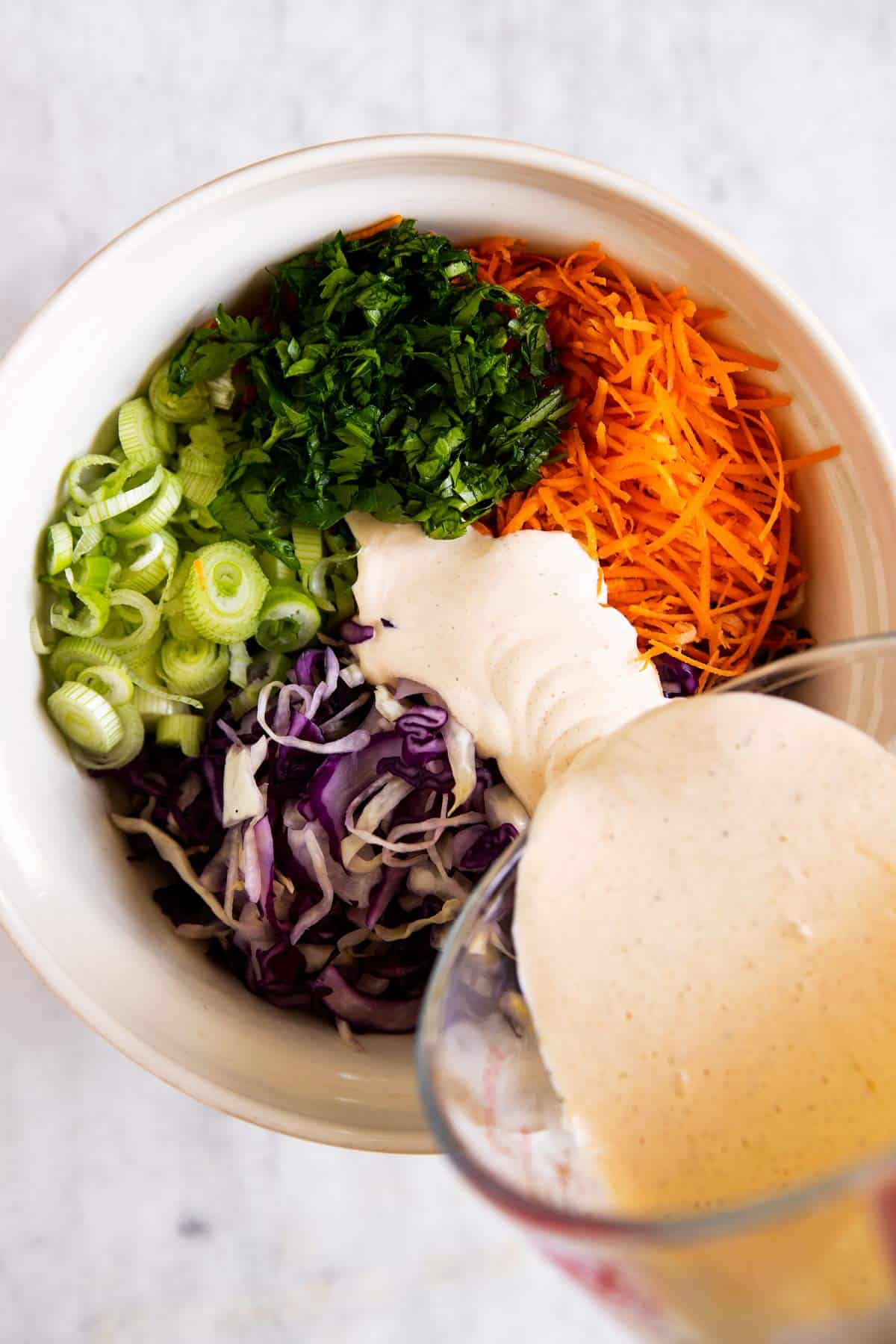 pouring dressing over coleslaw ingredients